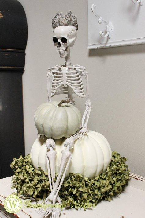 a creative Halloween decoration of a skeleton sitting on pumpkins and some greenery is very stylish