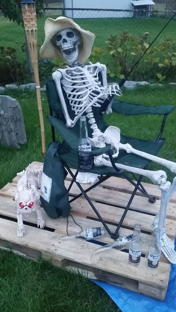 a fisherman skeleton in a chair plus a skeleton dog is a nice backyard decoration for Halloween