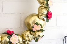 a gold skull wreath with flowers and greenery is an elegant and refined Halloween decoration