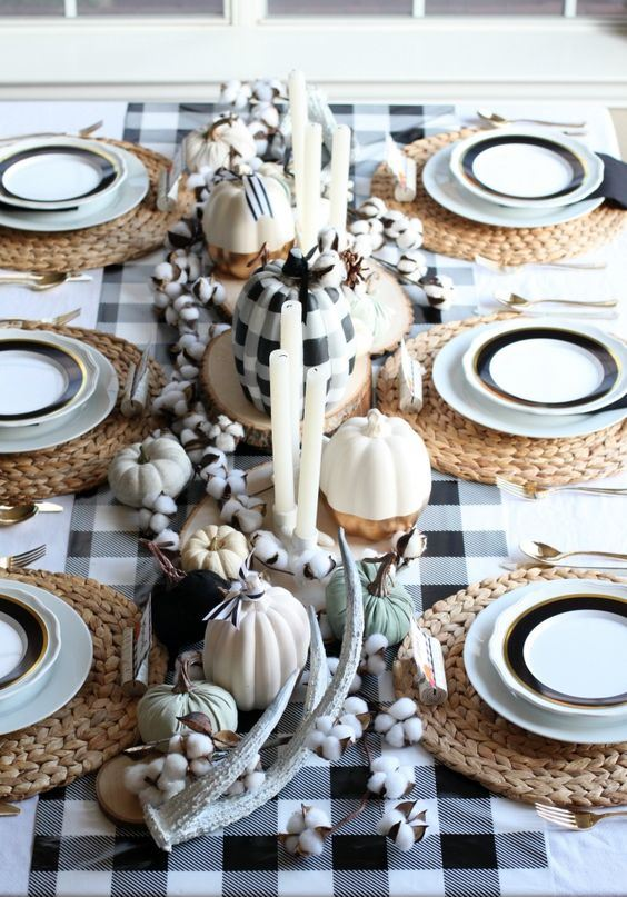 a gorgeous plaid fall tablescape with a plaid tablecloth, woven placemats, faux white and plaid pumpkins, cotton and antlers