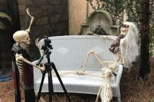 a hilarious Halloween decoration of skeletons and a skeleton cat taking photos
