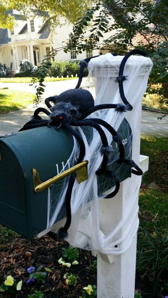 a large black spider and spiderwebs covering the mail box is a nice decoration for Halloween
