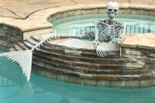 a mermaid skeleton is a gorgeous Halloween decor idea for those who have a pool in the backyard