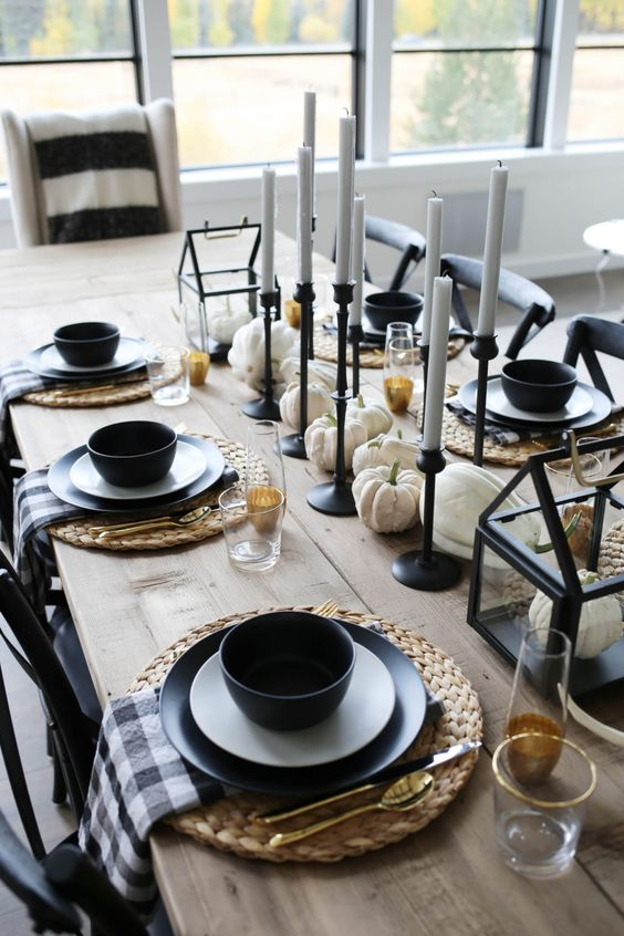 a modern fall tablescape with thin and tall candles, white pumpkins, black plates and bowls, plaid napkins and other black touches