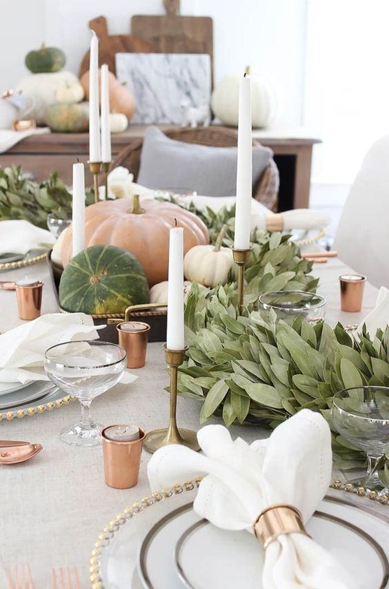 a neutral farmhouse table setting with copper candleholders, brass candleholders, a greenery runner and natural pumpkins