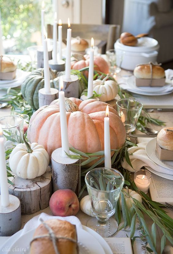a relaxed farmhouse tablescape with natural pumpkins, veggies and fruit, thin candles, tree stumps and greenery