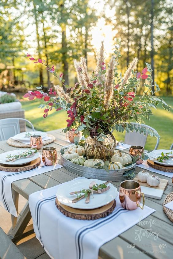 a relaxed natural tablescape with wood slices as placemats, a lush leaf, grass and berry arrangement and copper mugs