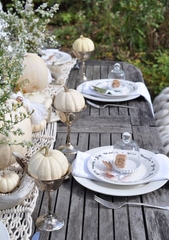 a relaxed outdoor fall tablescape with a macrame runner, white pumpkins and blooms, white plates and napkins