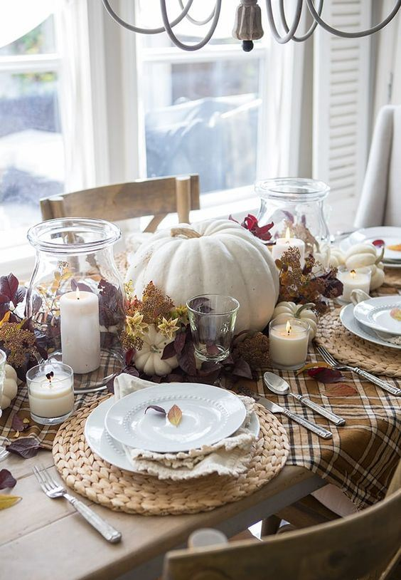 a rustic fall tablescape with a plaid table runner, a woven placemat, neutrla linens, naturla pumpkins, leaves and candles