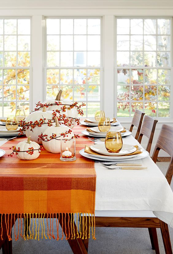 a simple and bright fall table setting with a striped runner, white pumpkins with berries, candles and stained glasses