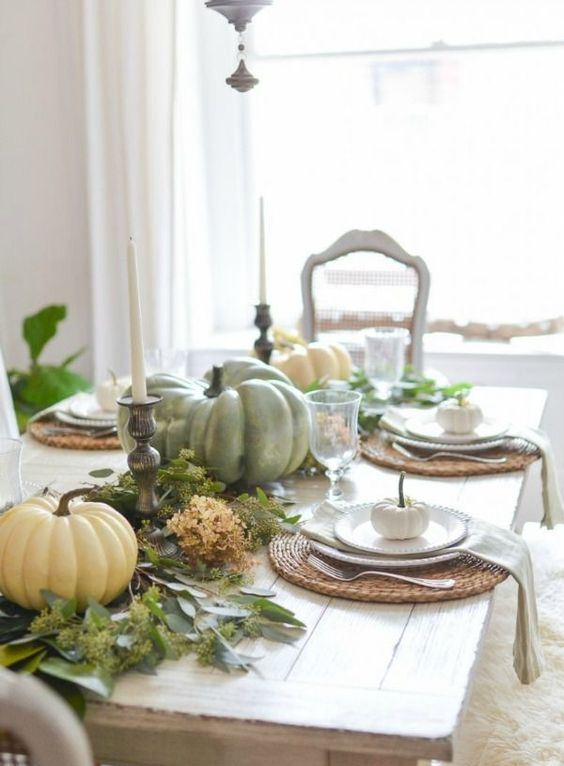 a simple rustic fall tablescape with a greenery and dried bloom runner, natural pumpkins and candles and woven placemats