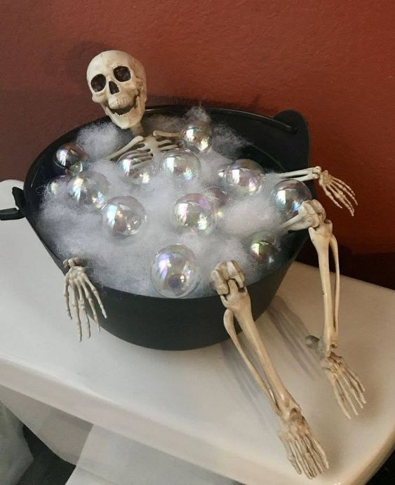 a skeleton in a cauldron with faux fur and ornaments to imitate bubbles for Halloween decor