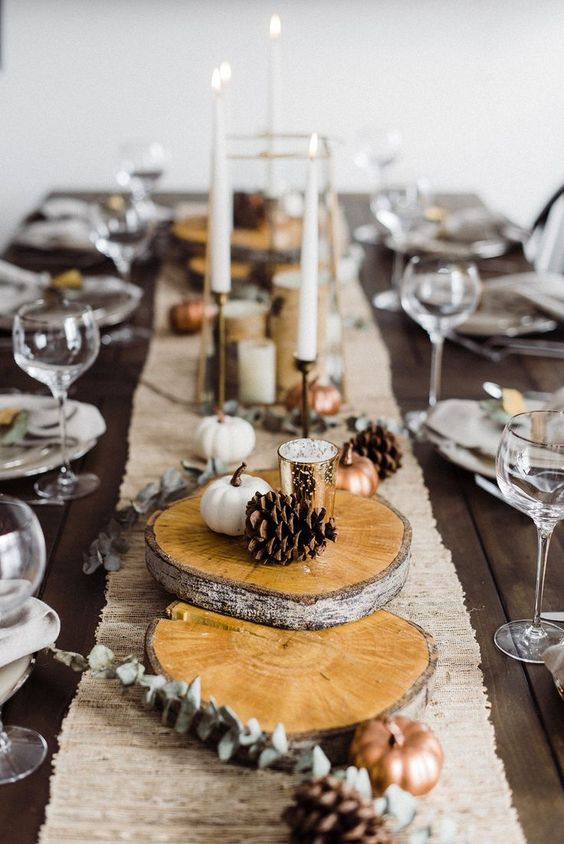 a stylish fall table setting with a burlap runner, wood slices, pinecones, mini faux pumpkins, thin candles
