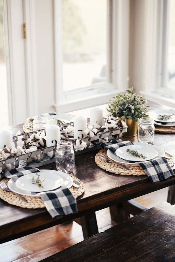 a stylish farmhouse fall tablescape with woven placemats, a cotton and candle centerpiece with greenery