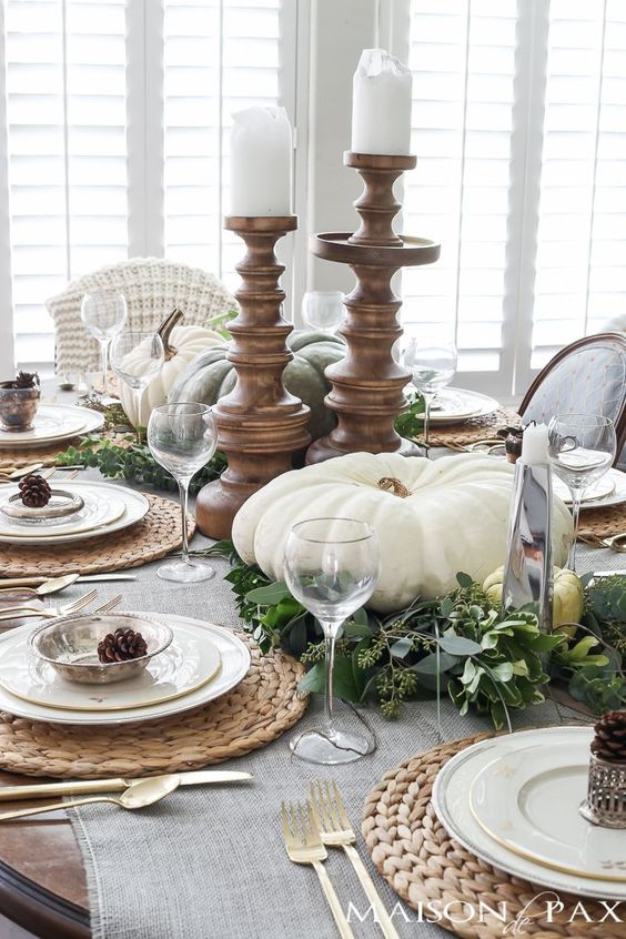 a stylish neutral fall tablescape with greenery and natural pumpkins, candles in wooden candleholders, woven placemats and pinecones