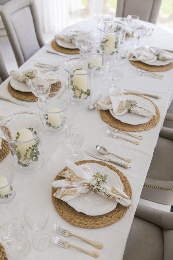 a very neutral fall tablescape with woven placemats, candles with greenery and printed napkins