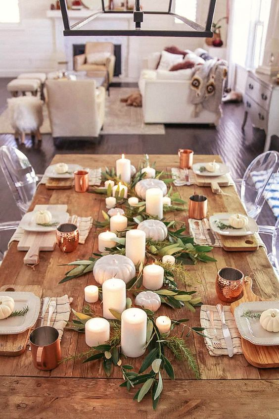 a very simple rustic tablescape with greenery, candles, white pumpkins, copper mugs and printed napkins