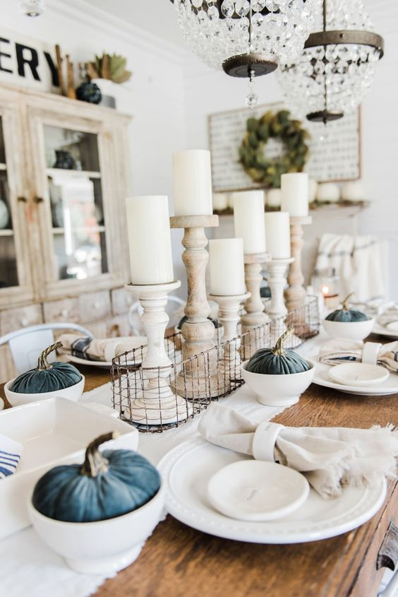 a vintage neutral fall tablescape with blue velvet pumpkins, white candles in wooden candleholders and neutral linens