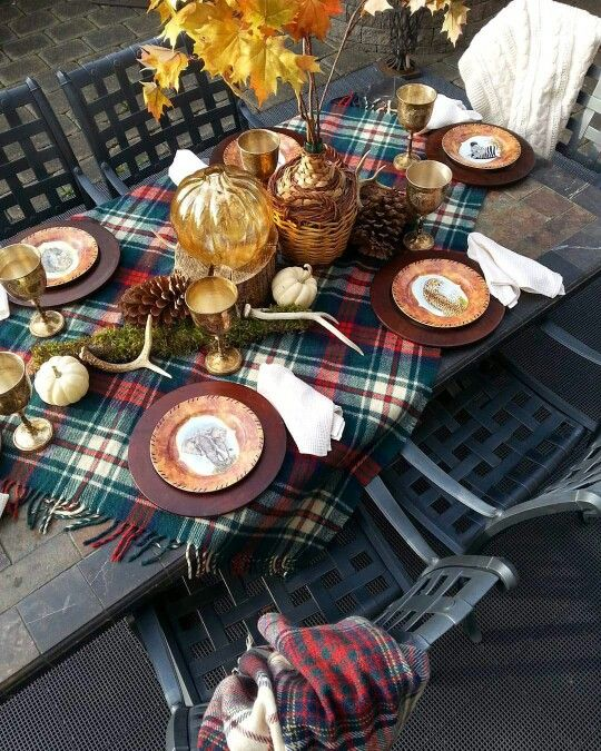 a woodland fall table setting with a bright plaid runner, metallic chargers, antlers, moss, pinecones and bright fall leaves