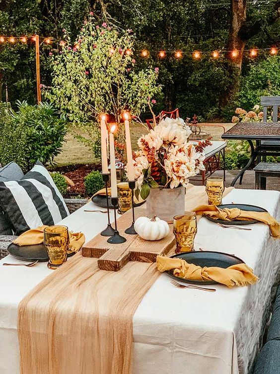 an easy modern fall tablescape with a rust runner and rust napkins, orange glasses, candles, white pumpkins and blush blooms