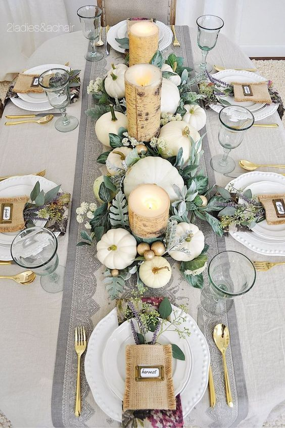an elegant neutral fall tablescape with neutral linens, white and gilded faux and real pumpkins, foliage, birch bark wrapped candles and gold cutlery