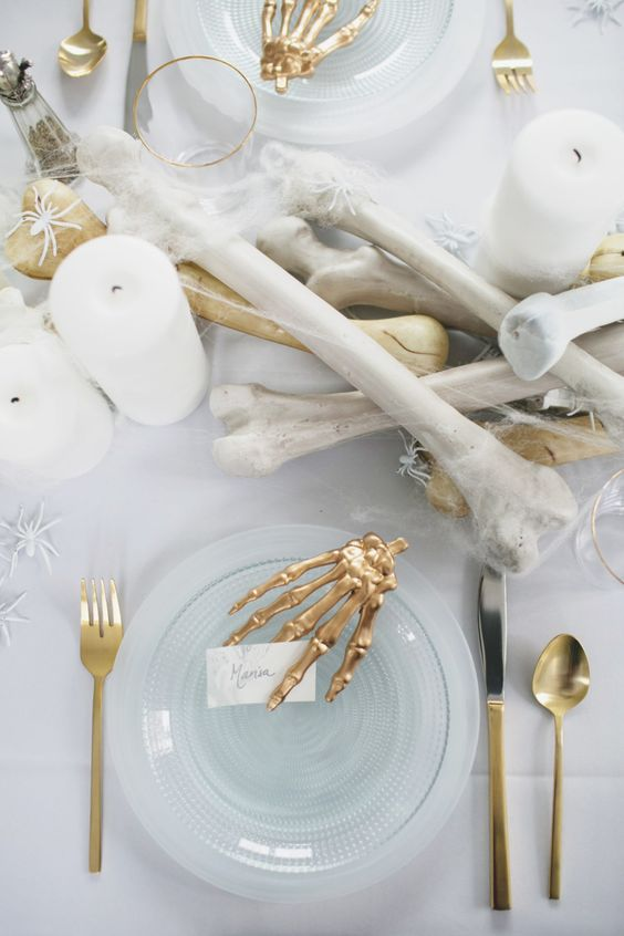 an elegant white Halloween table setting with bones, gilded skeleton hands, cutlery and white spiders