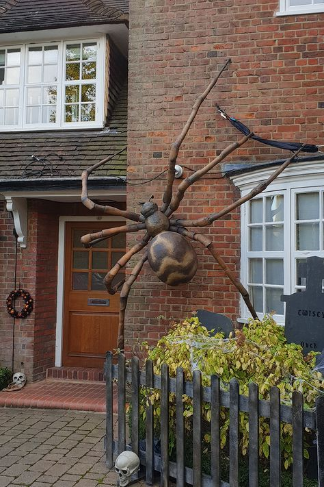 an oversized spider attached to a wall of your house is a lovely and spooky Halloween decoration