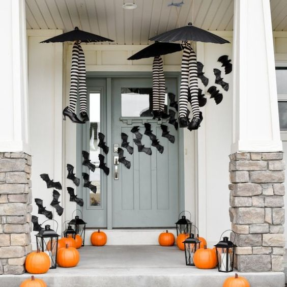 black paper bats, pumpkins and witches' legs in stockings make the front porch Halloween-like