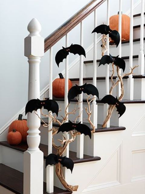 branches with black bats attached to the railing and pumpkins on the steps for Halloween decor