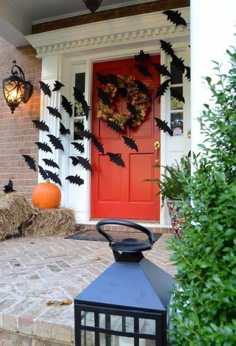 hay, pumpkins, black bats and a dried bloom wreath on the door make the front porch Halloween-like