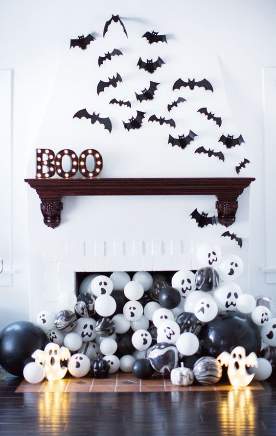 paper bats over the mantel, marquee letters and black and white balloons in the fireplace