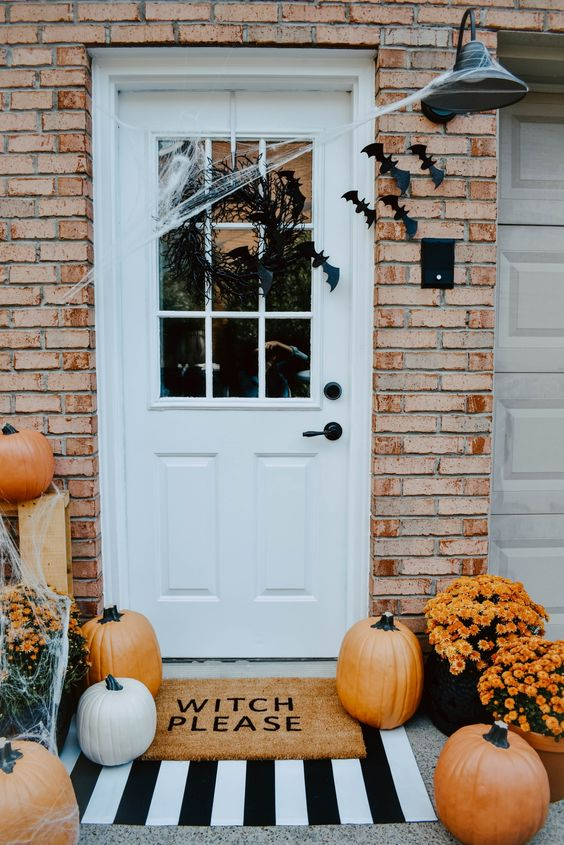 pumpkins, spiderwebs, bats, a vine wreath and bright potted blooms to get a gorgeous Halloween porch