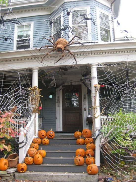 spiderwebs wtih large spiders and carved pumpkins create a stunning Halloween look for the front porch