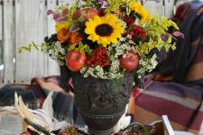 a bright fall arrangement with bold blooms, greenery, red apples and dark foliage placed in a tray with apples, gourds and pumpkins