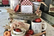 a cool fall decoration of a wooden stand with burlap leaves, red apples, printed fabrics, berries and wooden items