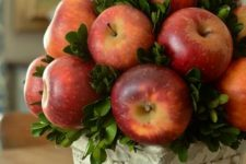 a cozy vintage fall centerpiece of a vintage urn, boxwood and red apples is a chic natural fall decoration