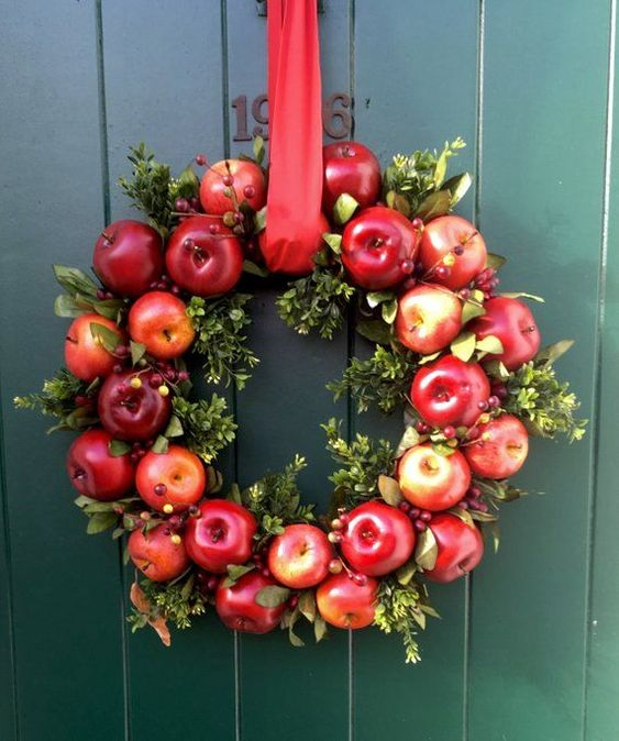 a fall wreath of boxwood, red apples, berries and a red ribbon is bright, fun and a bold option