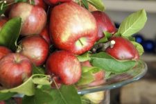 a glass bowl with foliage and red apples is a chic natural centerpiece you can make for the fall