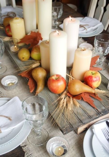 a harvest fall centerpiece of a wooden board, wheat, apples, pears, leaves and pillar candles is amazing