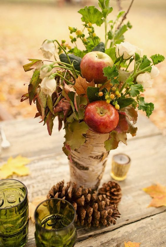 a natural fall centerpiece of a tree stump, apples, greenery, berries and white blooms plus pinecones is a super cool