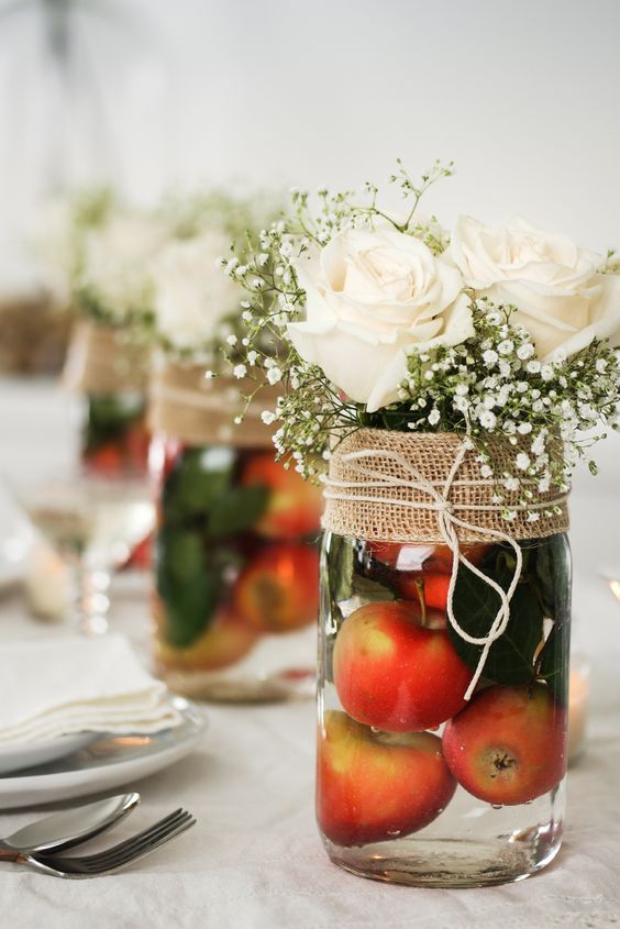 a pretty fall wedding or party centerpiece of apples in a jar, foliage, baby's breath, white roses and burlap
