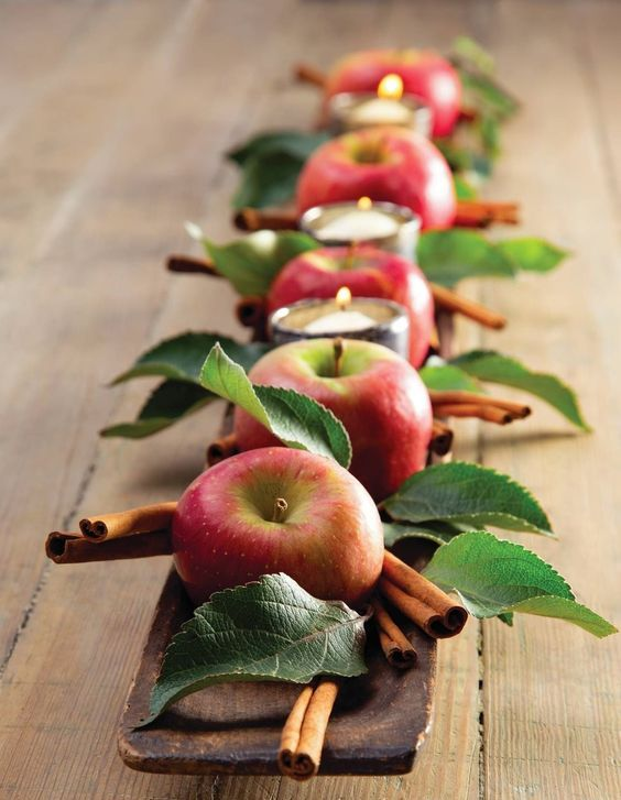 a rustic centerpiece of a long wooden bowl, foliage, cinnamon sticks, apples and candles in candleholders