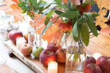 a rustic fall centerpiece of a wooden board with apples, candles, foliage and fall leaves in vases is easy to make