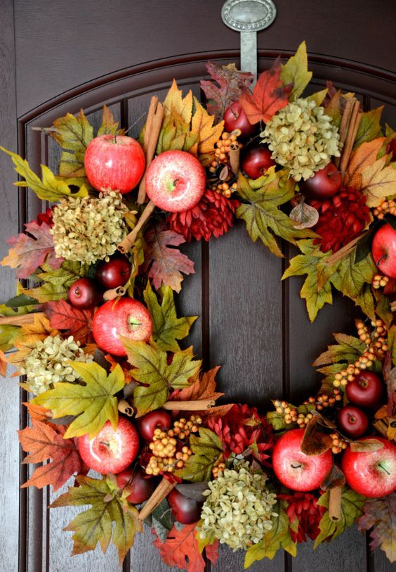 a rustic fall wreath of faux leaves, berries, apples, blooms and cinnamn sticks is lush and amazing