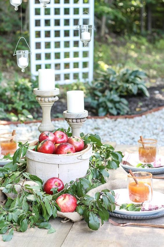 a wooden basket with red apples and lush foliage, a couple of candles in wooden candleholders for a fall centerpiece
