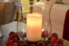 an oversized candle lantern surrounded with red apples is an easy and long-lasting fall centerpiece