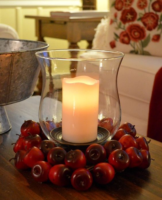 an oversized candle lantern surrounded with red apples is an easy and long lasting fall centerpiece
