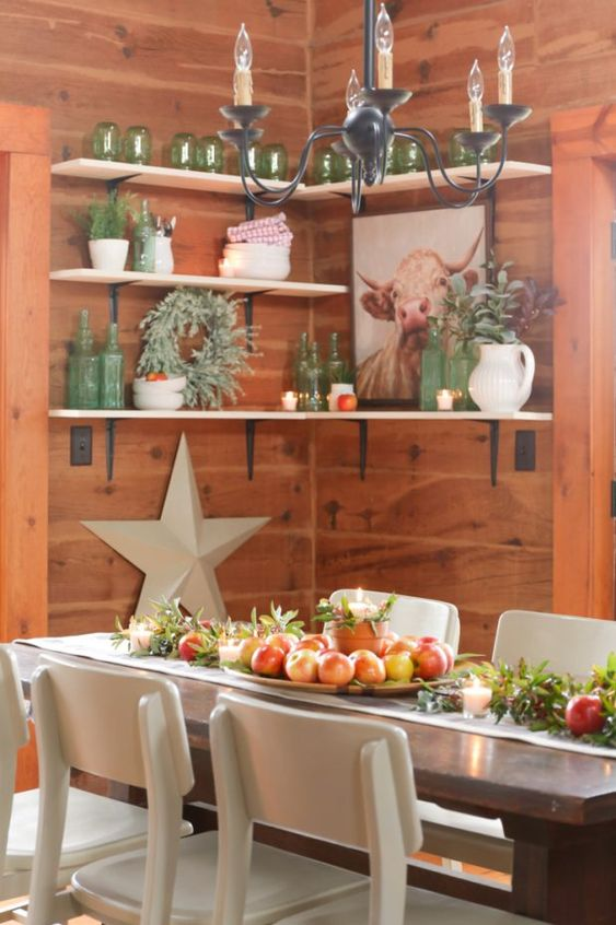 farmhouse fall decor with greenery, apples, a wooden tray with apples and a planter with a candle