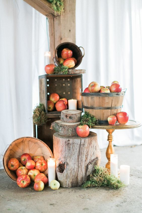 pretty woodland and rustic decor with apples in wooden baskets, moss, tree slices and stumps, candles on the floor