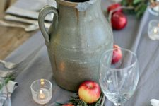 rustic table decor with a grey table runner, a vintage jug, apples and greenery right on the table